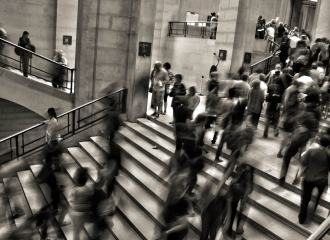 Blurred photo in B and W of people moving fast through stairs