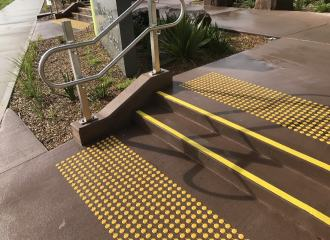 Yellow stair tread nosing strips on wet concrete, with yellow discrete tactile indicators on both stair landings