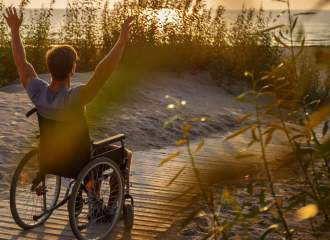 Young man using a wheelchair relaxing on the beach over sunset