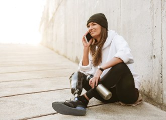A young fashionable girl sitting on a ramp using the phone, she wears a prosthetic lower leg