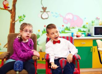 Two young kids, a boy and a girl, both with disabilities, sitting in a colourful classroom