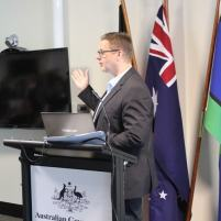 Lee Wilson speaking at a government conference, in front of the national flags